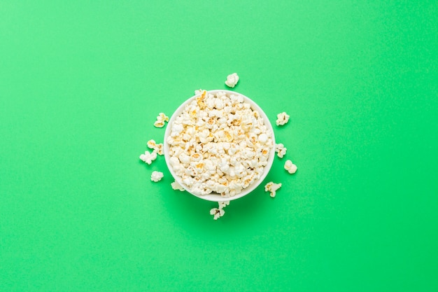 Чаша с попкорном на зеленом фоне. плоская планировка, вид сверху.