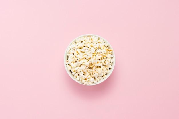 Чаша с попкорном на розовом фоне. плоская планировка, вид сверху.
