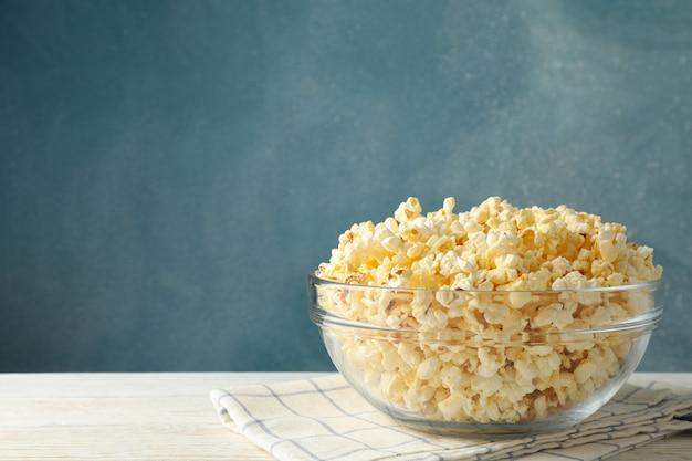 Чаша с попкорном на белом деревянном пространстве. пища для просмотра кино