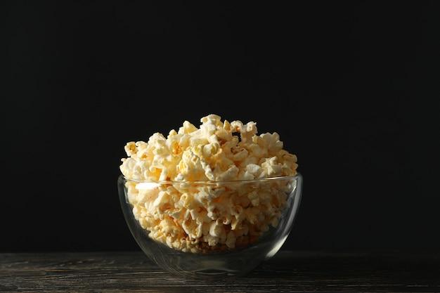 Чаша с попкорном на деревянный стол. пища для просмотра кино
