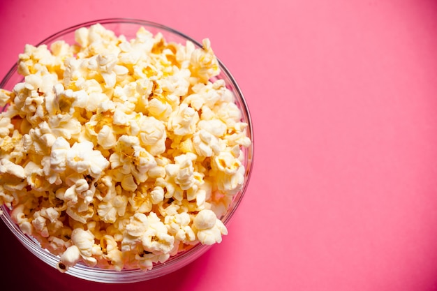 Bowl with popcorn on red background