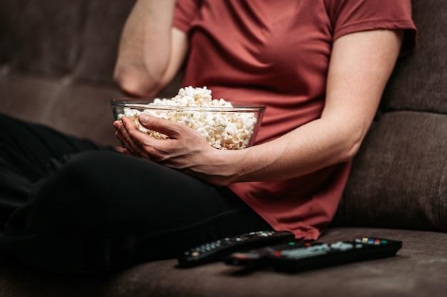소파에 tv 리모컨으로 영화를 보면서 팝콘 그릇