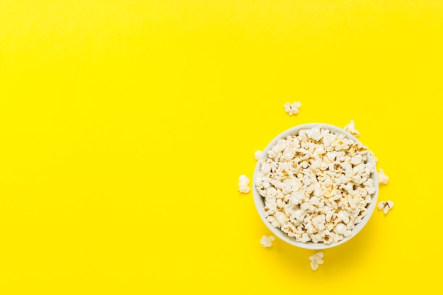 Bowl with popcorn on a yellow background. flat lay, top view.