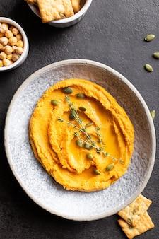 호박 후무스를 곁들인 그릇, 채소와 향신료로 장식된 맛있는 전채