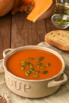 カボチャのスープとボウルは、木製の背景に食材を使った荒布の種を添えてください。
