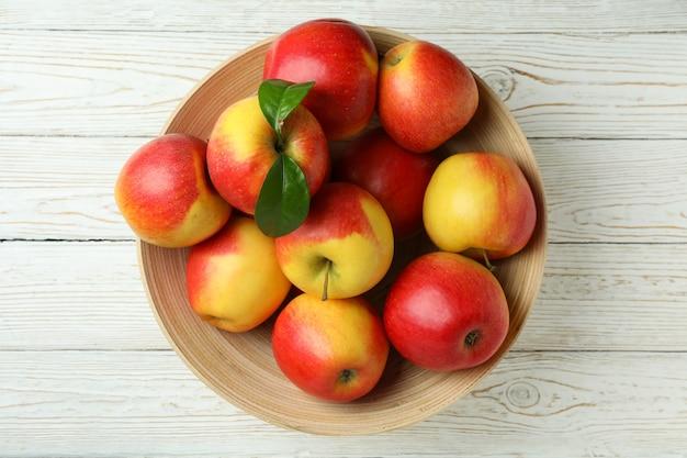 白い木製のテーブルに赤いリンゴのボウル