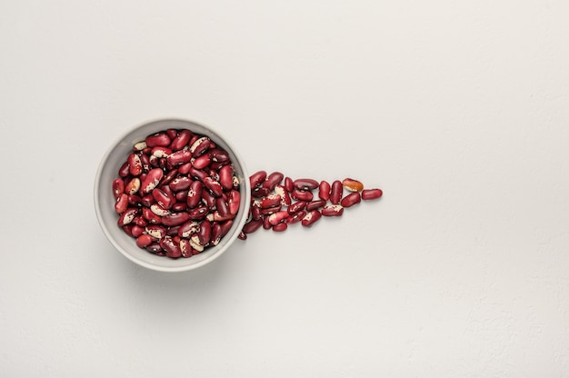 Bowl with red beans on a light textured surface next to the grain is poured in the form of an