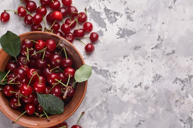 Bowl with red cherries on gray background.