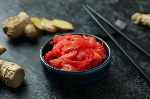 Bowl with red pickled ginger and chopsticks on black smokey