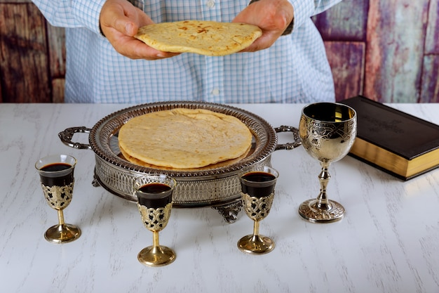 Bowl with red wine, bread and bible during prayer for bread holy communion