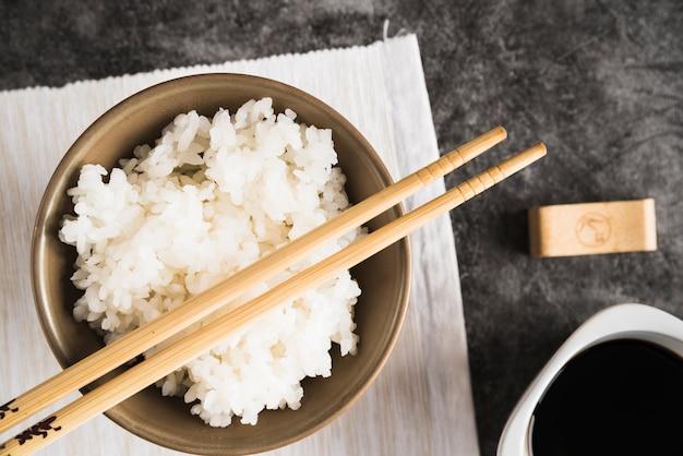 Чаша с рисом и палочками на салфетке под соевым соусом