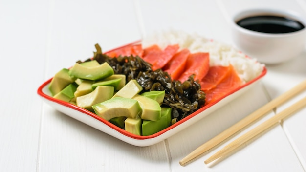 Bowl with rice, avocado, salmon and kelp on a white table.