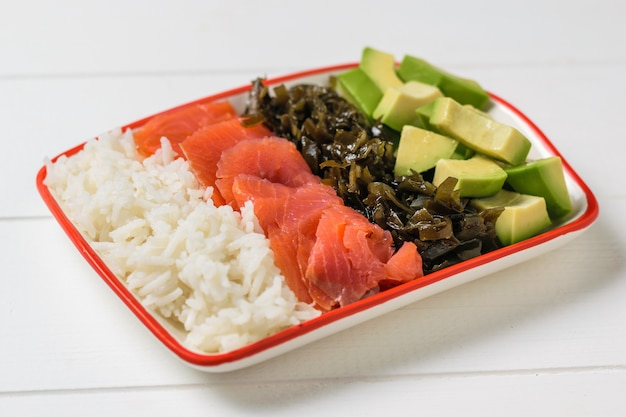 Bowl with rice, avocado, salmon and kelp on a white wooden rustic table.
