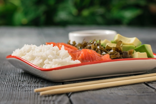 ボウルにご飯、アボカド、海藻、サーモンの木製テーブル