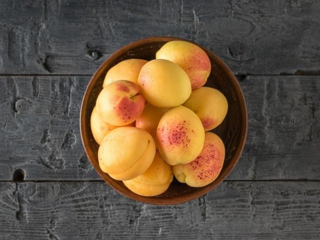 Чаша со спелыми абрикосами в центре деревянного стола. урожай свежих фруктов.