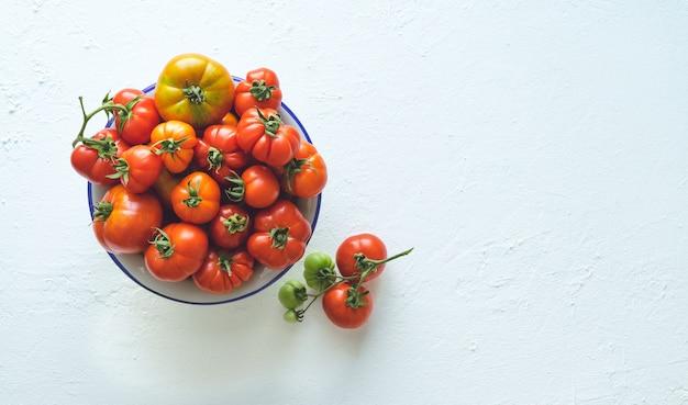 Чаша со спелыми помидорами на белом фоне копией пространства.