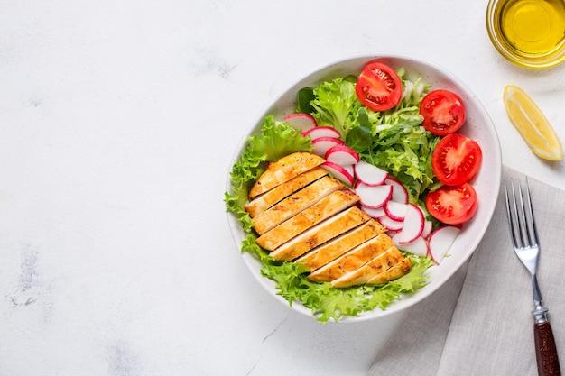 Чаша с салатом и нарезанным куриным филе. диетический обед, кето-диета, здоровое питание. вид сверху на белом фоне.