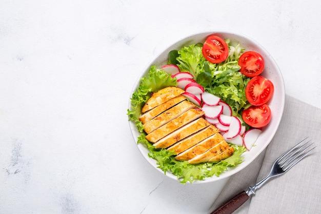 サラダとスライスした鶏肉の切り身を入れたボウル。ダイエットランチ、ケトダイエット、健康食品。上面図。