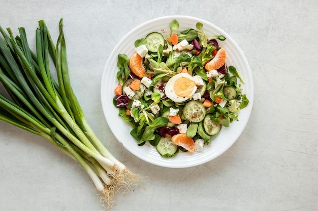 Ciotola con insalata e cipolla verde accanto