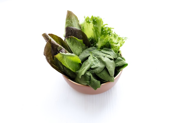 Чаша с листьями салата из шпината, салата и романа на белом фоне