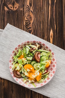 Bowl with salad standing on napkin