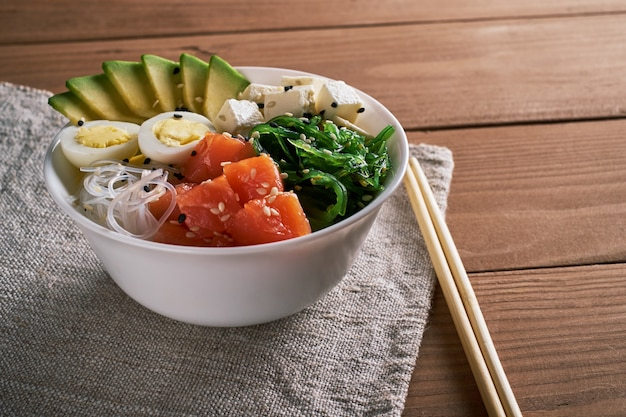 Bowl with salmon avocado sesame with chopsticks  linen napkin tablecloth