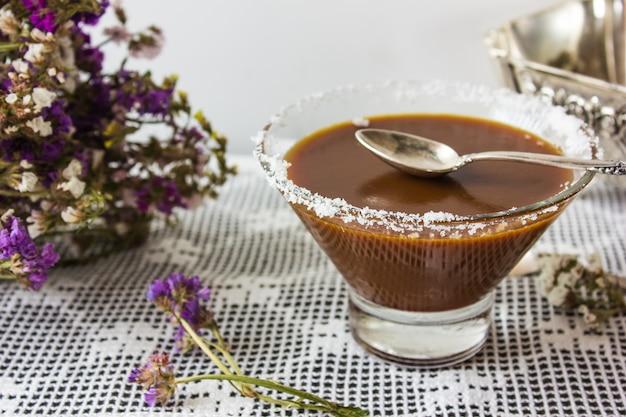 Чаша с соленой карамелью и конфеты на деревянном фоне, вид сверху