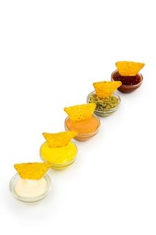 ナチョスコーンチップスを添えた白い皿にソースをかけたボウル。白い背景の上の分離。
