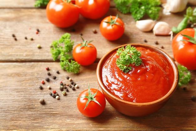 나무 테이블에 소스, 토마토, 녹지, 향신료와 그릇