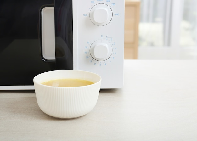 Bowl with soup near microwave on table
