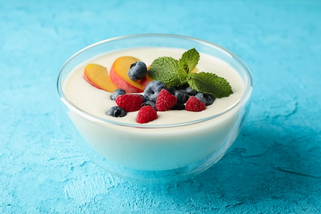 Bowl with sour cream yogurt and fruits on color background
