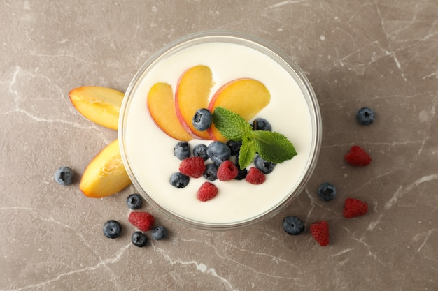 Bowl with sour cream yogurt and fruits on grey background