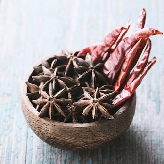 Bowl with stars anise and red chilli pepper on blue old wood