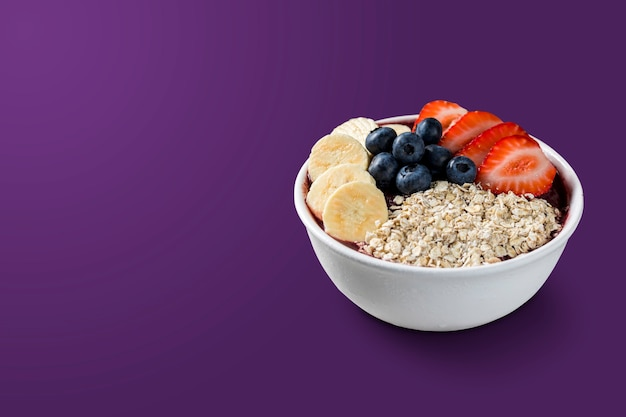 Bowl with strawberries, bananas, blueberry and granola. isolated on purple background. summer menu front view.