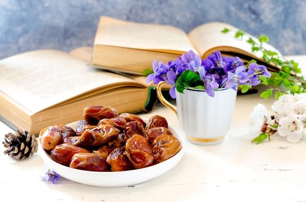 Чаша со сладкими вкусными сушеными финиками в композиции с фиолетовыми цветами и старинными книгами