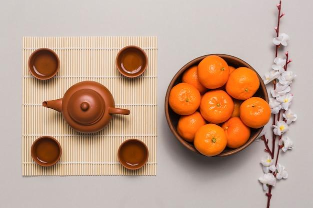 Bowl with tangerines near tea set
