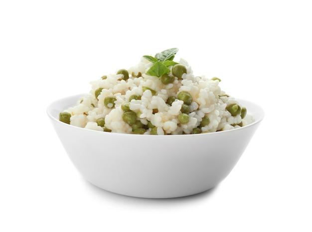 Чаша с вкусным отварным рисом и горохом на белой поверхности