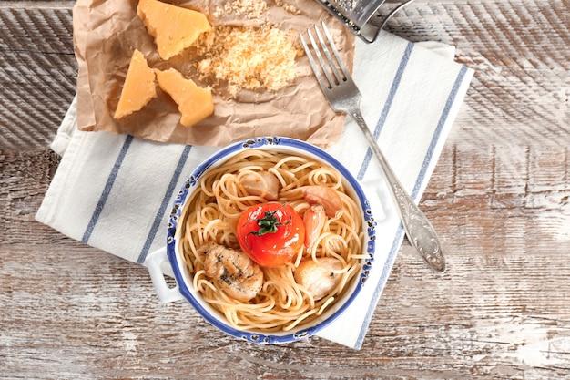 Чаша с вкусными куриными спагетти на деревянном столе