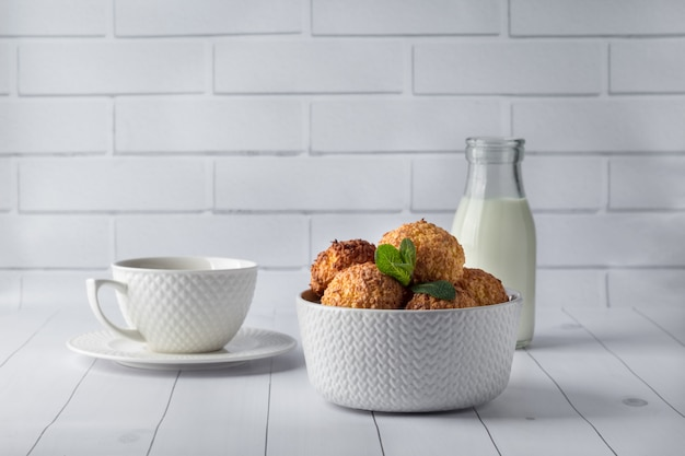Bowl with tasty coconut cookies and drinks on white wooden table