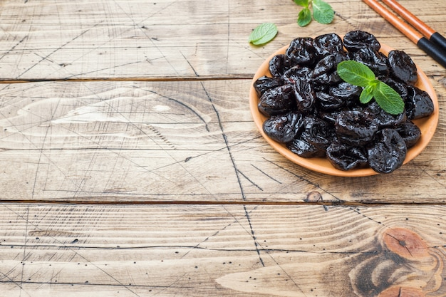 Bowl with tasty dried plums on wooden table copy space