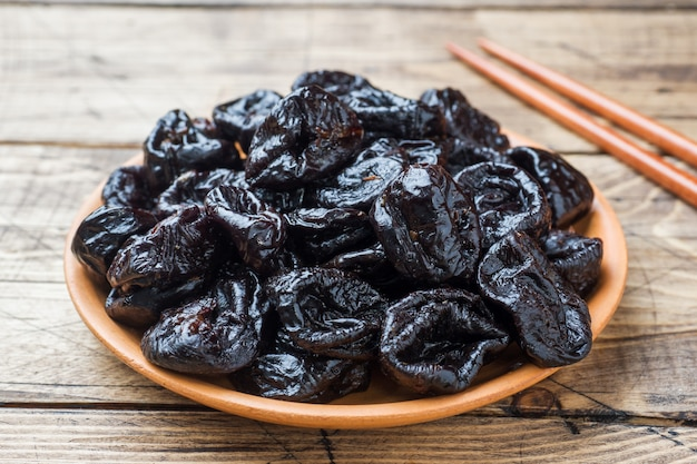 Bowl with tasty dried plums on wooden table