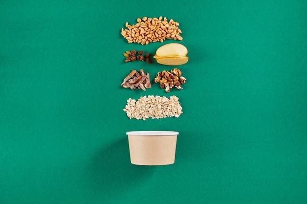 Миска с вкусной мюсли и ингредиентами. вид сверху на бумажную чашу. концепция нулевых отходов.