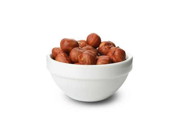 Bowl with tasty hazelnuts isolated on white wall