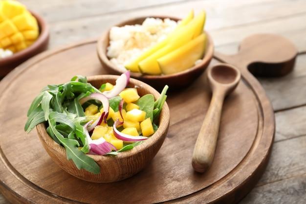 Чаша с вкусным салатом из манго на деревянном столе