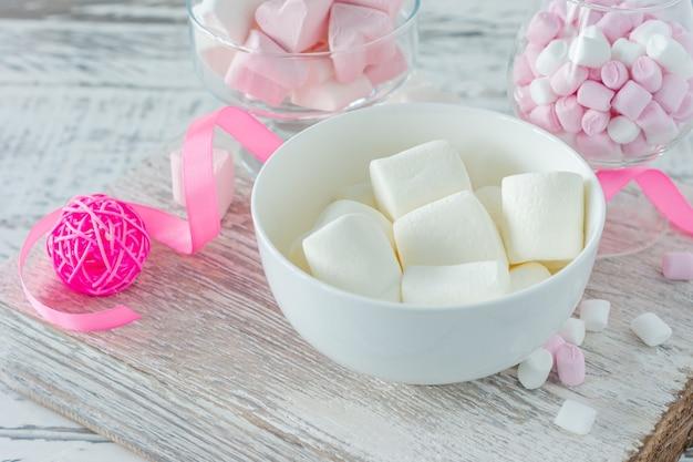 白いテーブル、クローズアップにおいしいマシュマロとピンクのリボンのボウル。