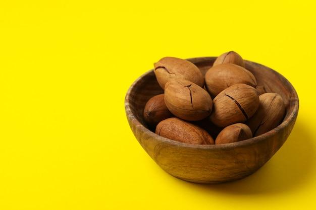 Чаша с вкусными орехами пекан на желтом