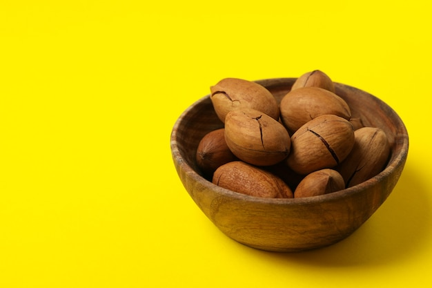 Bowl with tasty pecan nuts on yellow