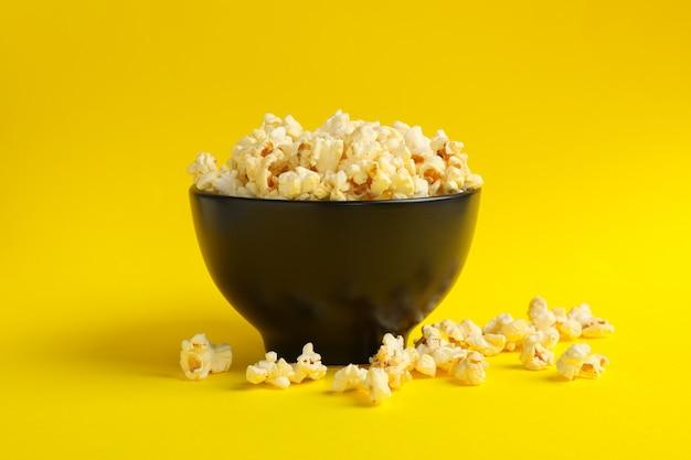 Чаша с вкусным попкорном на желтом пространстве. пища для просмотра кино