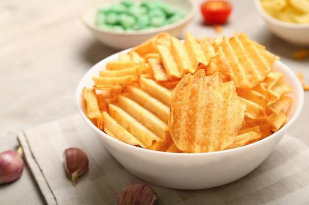 테이블에 맛있는 감자 칩과 그릇
