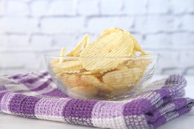 나무 배경에 맛있는 감자 칩과 그릇